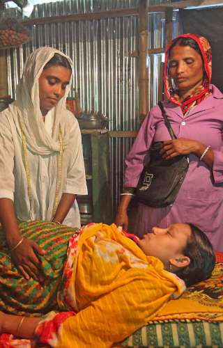 A BRAC community health worker performs an ante-natal health check-up on a mother in Bangladesh.
