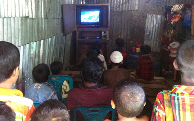 Children of all ages watch Doraemon together in the tin-shed clubhouse set up by a microfiance client.