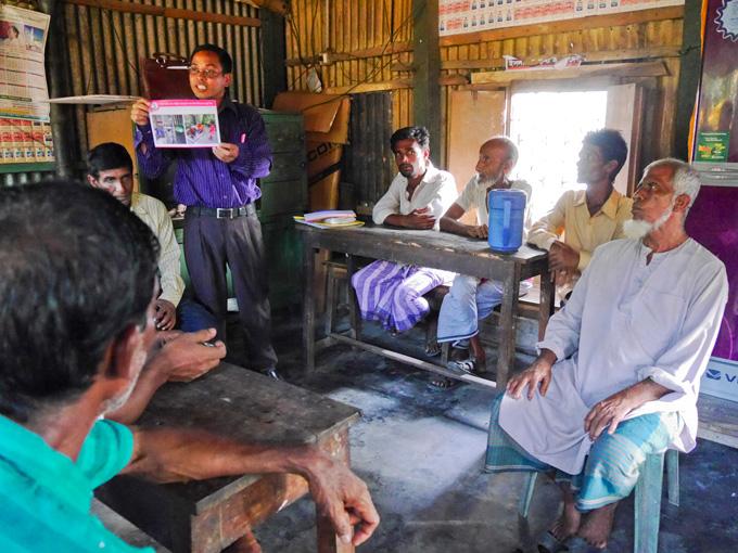 Horan Chandra, BRAC field organiser engages the men in discussion at a tea stall in Kaliganj