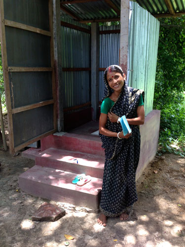 A client stands in front of the latrine that she was able to build with the help of a loan from BRAC.
