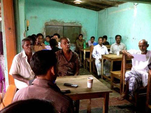 While taking a short break from work in the afternoon, men attend a BRAC WASH tea stall meeting.