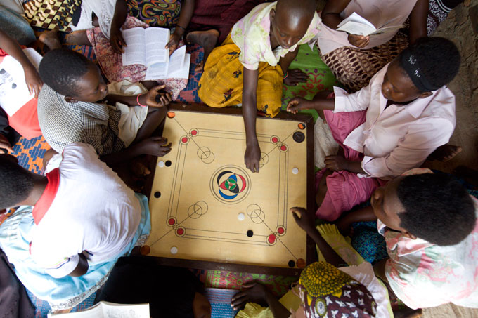 Members of an ELA club in Uganda gather around to play carom board, a popular indoor game.