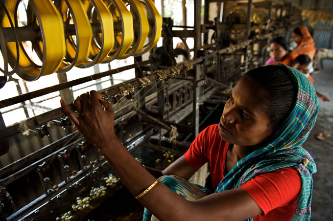 A BRAC Silk worker extracts fine silk from cocoon at a reeling centre in Rangpur district