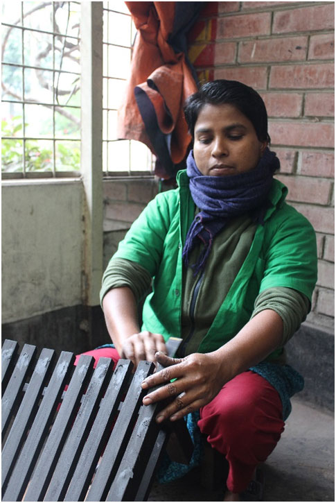 Fatema working at the wood section of Ayesha Abed Foundation