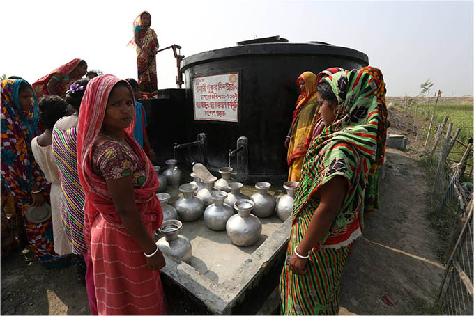 Women from the community gather around a pond sand filter built by BRAC.