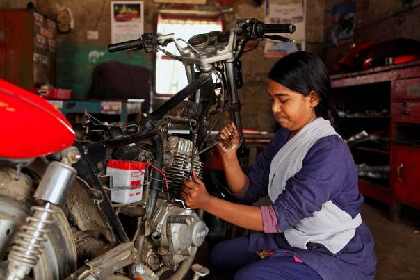 Khadija Akhter, an 18-year-old mechanic, fixes a motorbike at a workshop in Rajshahi in northern Bangladesh.
