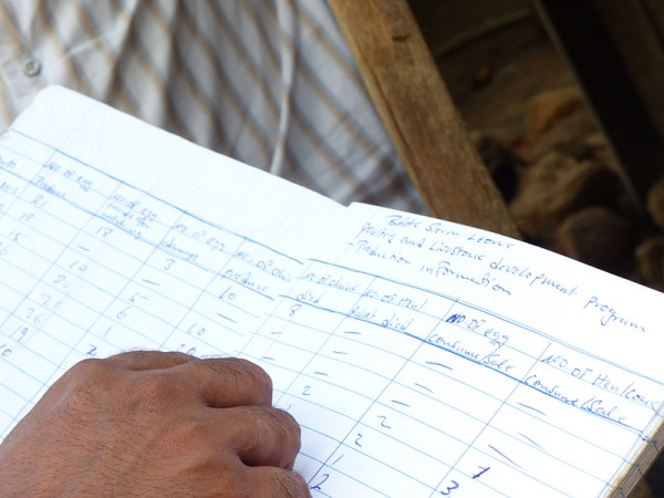 Reviewing a poultry accounting logbook with BRAC clients in Sierra Leone. (Photo: BRAC/Rod Dubitsky)
